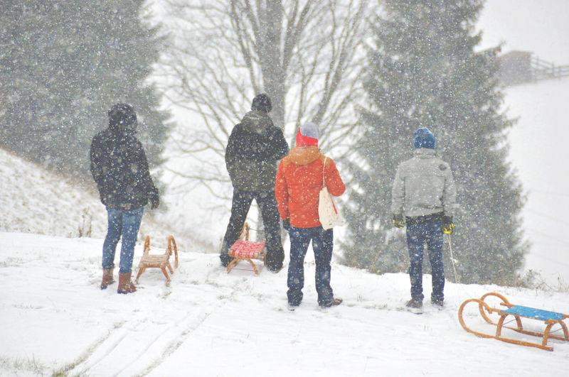 Rear View Of People Walking On Snowed Landscape