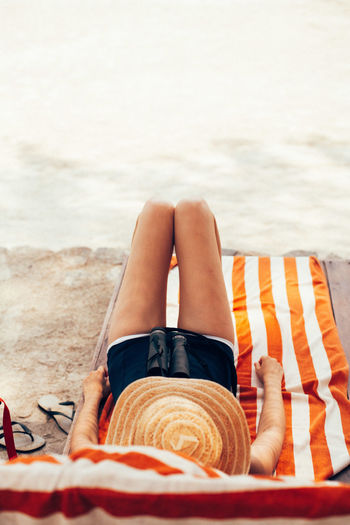 Low section of woman lying on sand at beach