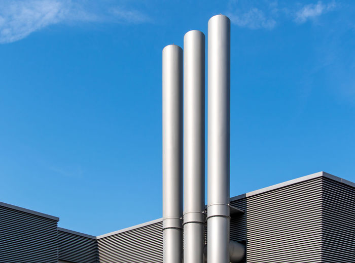 Low angle view of smoke stacks on building against sky