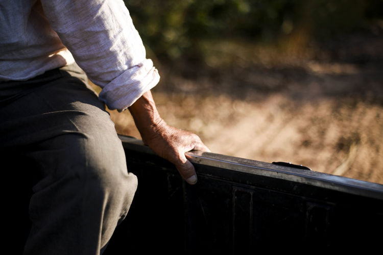 Midsection of man sitting on metal