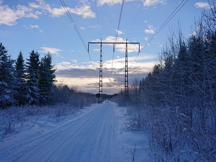 Electricity pylon by snow covered trees against sky