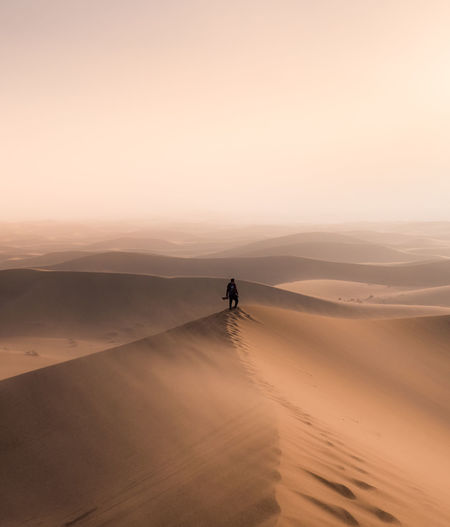 Man standing at desert against sky during sunset