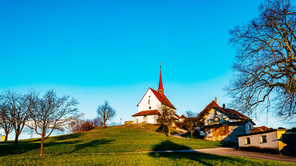 Architecture Bare Tree Blue Building Exterior Built Structure Church Clear Sky Copy Space Field Gormund Grass House Kapelle Outdoors Place Of Worship Religion Sky Spirituality Sunlight Tree