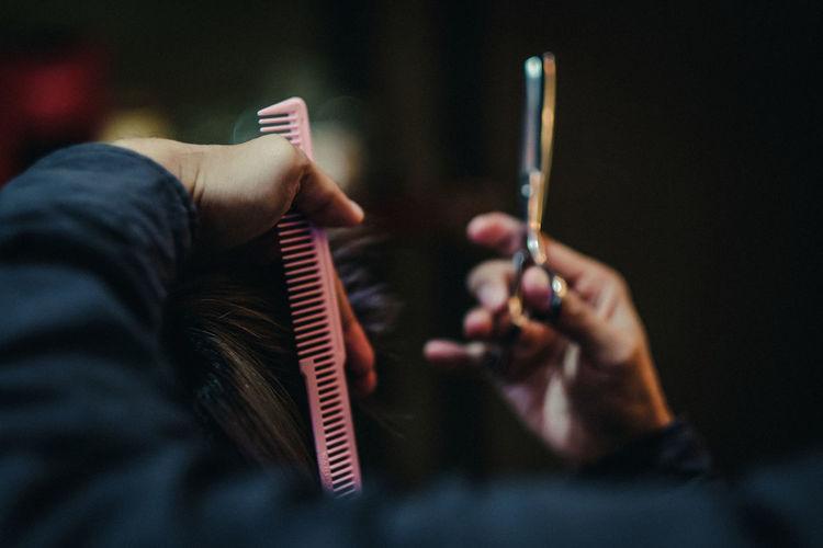 Hairdresser cutting customer hair in salon