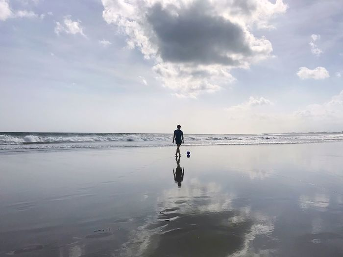 Silhouette man walking at beach against sky