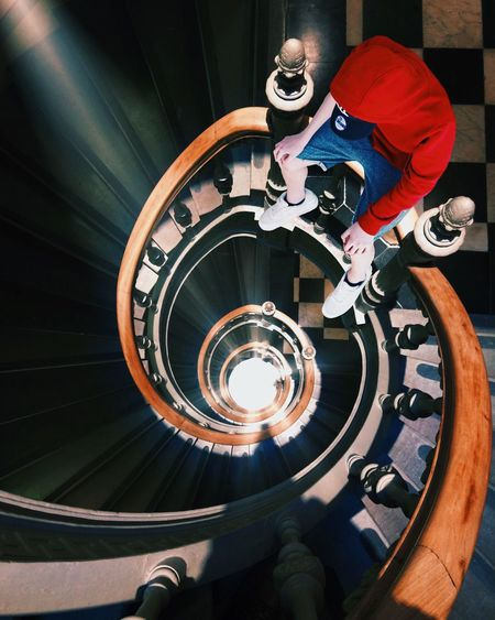 High angle view of man in red hooded short sitting on spiral steps railing