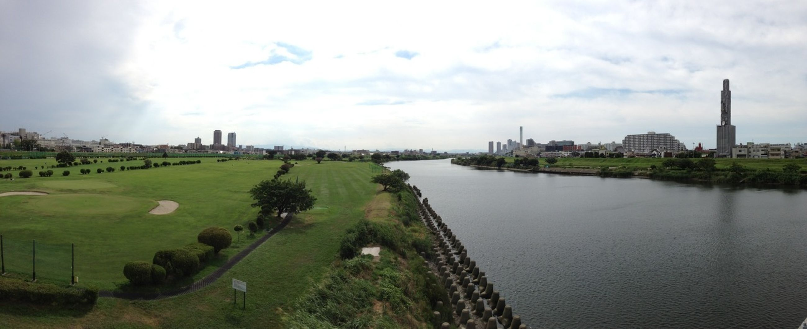 architecture, built structure, building exterior, sky, water, cloud - sky, river, cloudy, grass, history, tree, cloud, famous place, travel destinations, city, tower, day, nature, travel, outdoors