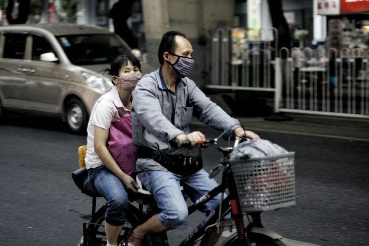 在马路上行走的电瓶车. Battery Bike Mask 电瓶车上的中国人