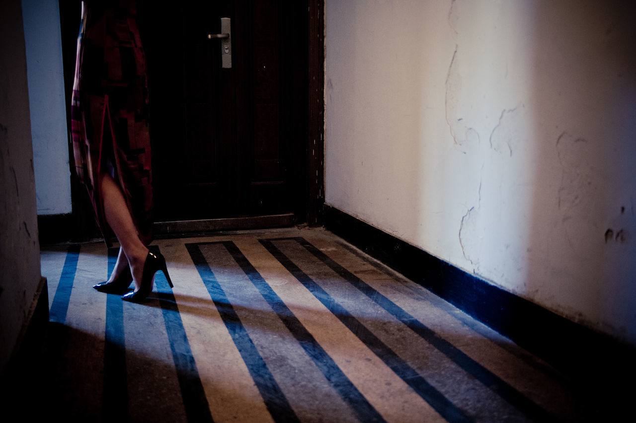 one person, real people, flooring, indoors, low section, body part, human body part, human leg, shadow, home interior, entrance, sunlight, lifestyles, door, women, day, standing, architecture, domestic room, tiled floor, human foot