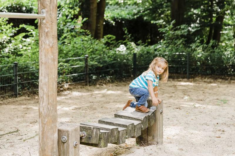 Full length of girl standing on outdoor play equipment in park