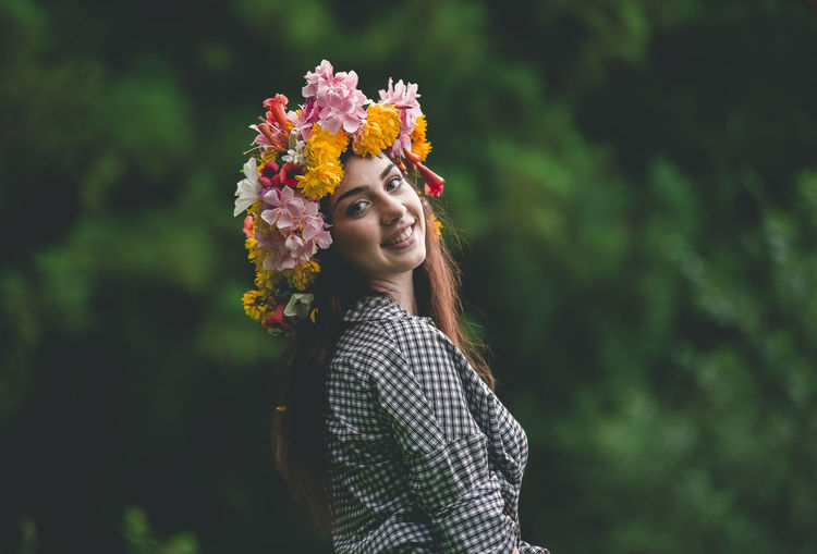 Portrait of smiling young woman wearing flowers against trees