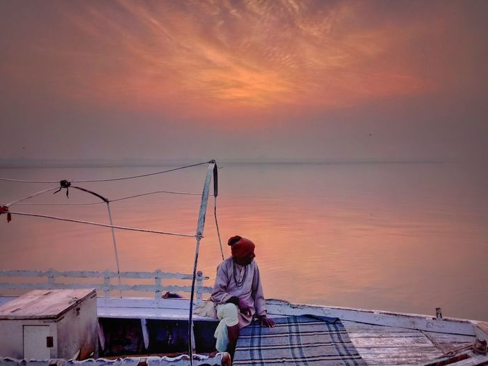 Full length of mature man sitting in boat on sea against sky during sunset