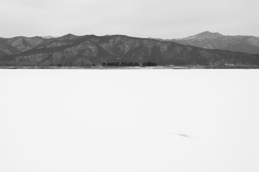 black and white image of snow-covered lake, Uiamho Lake in Chuncheon, Gangwondo, South Korea Black & White ChunCheon Cold Lake Cold Weather Gongjicheon Snow Land Uiamho Lake Winter Winter Landscape Beauty In Nature Black And White Blackandwhite Bw Cold Cold Temperature Day Lake Landscape Mountain Mountain Range Nature No People Outdoors Scenics Sky Snow Snow-covered Snow-covered Lake Tranquil Scene Tranquility Winter Winter Lake Winter Land Winter Time