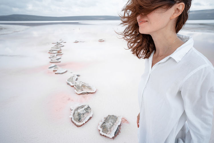 Midsection of woman standing on beach