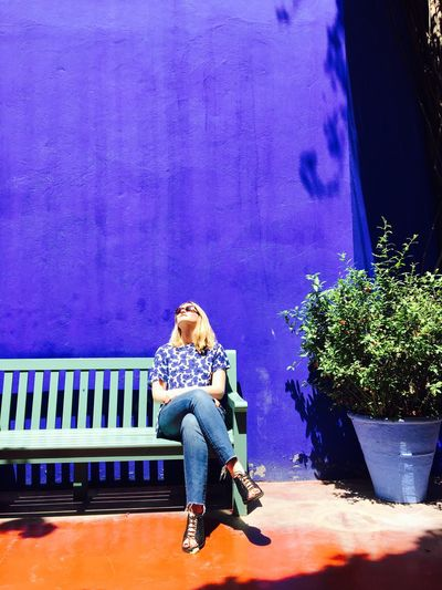 Fashionable woman sitting on bench against purple wall
