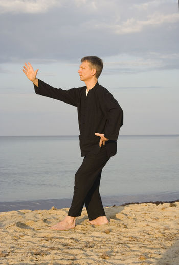 Mid adult man practicing tai chi at beach against sky