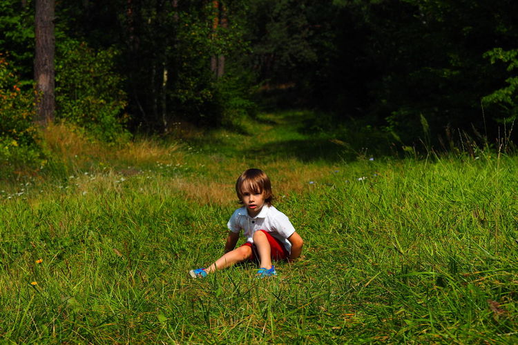 Picture of a little boy sitting on field