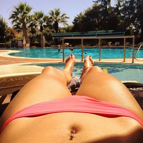 Low section of bikini woman lying at poolside