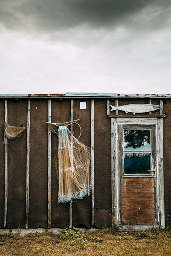 Clothes hanging on wall by building against sky