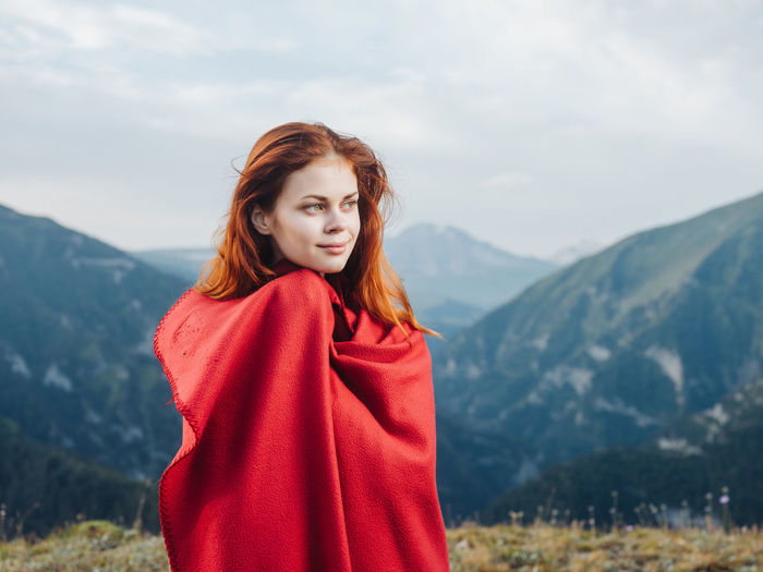 Portrait of beautiful young woman standing against mountains