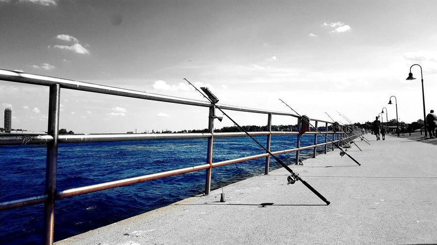 Fishing rods on railing by sea against sky