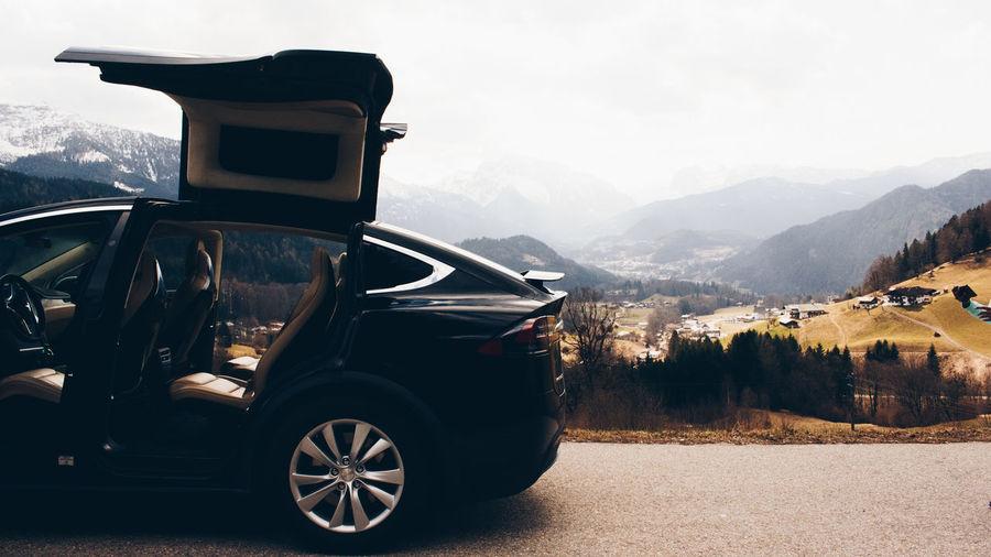 Vintage car on road against mountain range