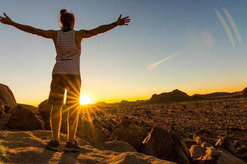 Rear view of man standing on landscape against sky during sunset