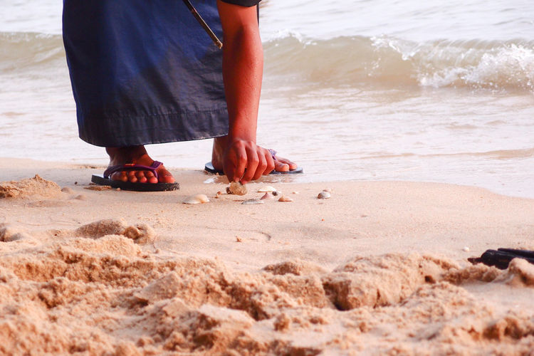 man touching the shells Wave Weather Adult barefoot Beach Body Part Day Human Body Part Human Foot Human Leg Human Limb Land Leisure Activity Lifestyles Low Section One Person Outdoors Real People Sand Sea Standing Touching Water Wet Women