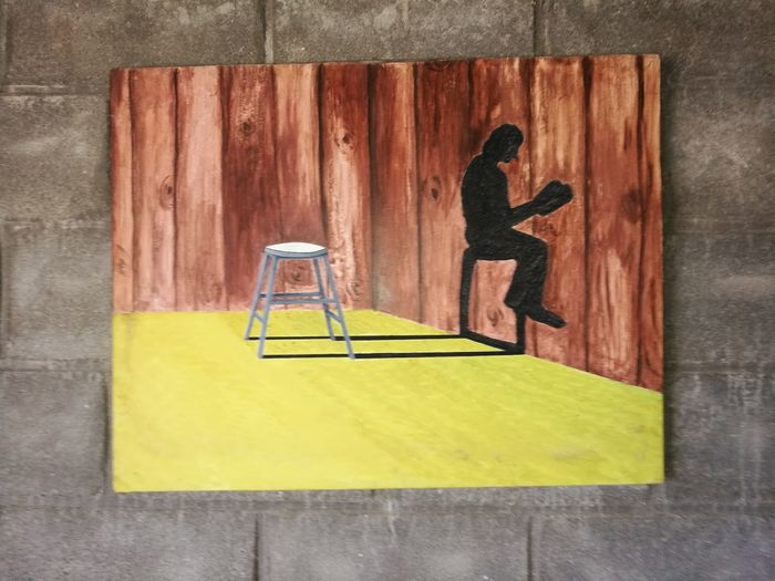 Full length of man using mobile phone on wall