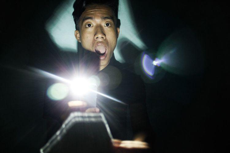 Portrait of young man holding illuminated flashlight in darkroom
