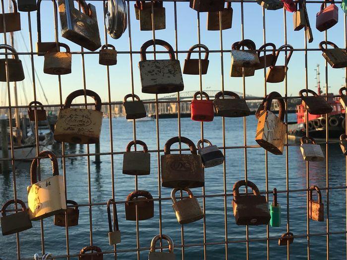 Close-up of padlocks hanging on sea against sky