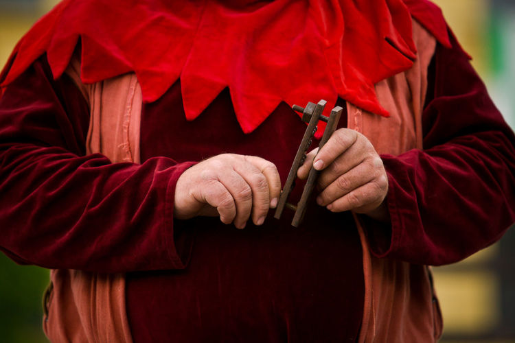 Thumbscrew Red Cape  One Person Midsection Holding Clothing Day Traditional Clothing Unrecognizable Person Standing Adult Outdoors Executioner Torture Torment Torture Device Middle Ages Middle Age Horrible Pain Hands Medieval Medieval Festival Executor
