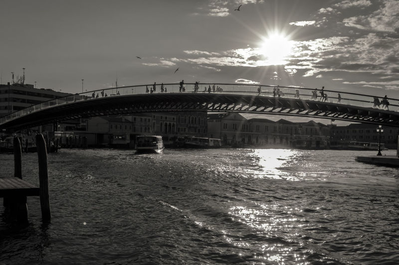 Modern Constitution Bridge (Ponte della Costituzione) over Grand Canal, black and white. The pedestrian bridge connects the north of the city with the mainland and the rail terminal. Be. Ready. Calatrava Costituzione Grand Canal Modern Venice, Italy Architecture Black And White Bridge Canal City Constitution Day Della Europe Nature Outdoors Pedestrian Ponte Santiago Sky Sun Sunlight Water Wave