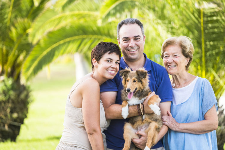 Portrait of happy friends with dog in park