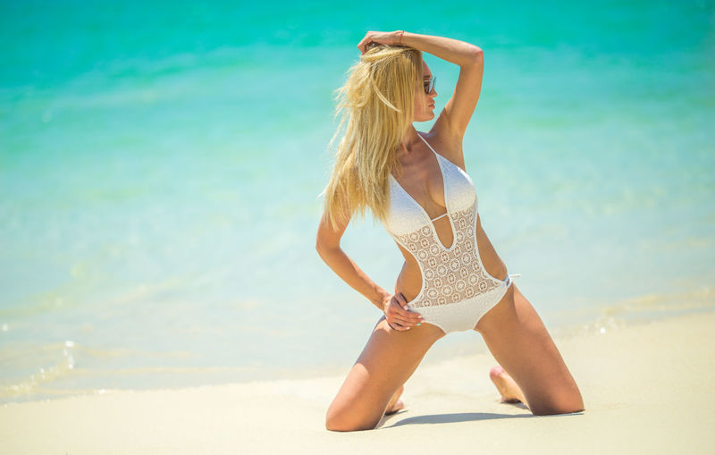 Beach Beautiful Woman Beauty Beauty In Nature Bikini Blond Hair Day Full Length Kneeling Kneeling Girl Leisure Activity Lifestyles One Person Outdoors Real People Rear View Sand Sea Sky Summer Sunlight Vacations Water Young Adult Young Women