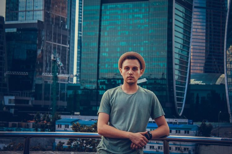 Portrait of young man standing against modern buildings in city