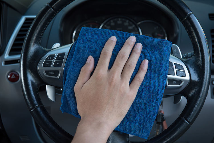 Cropped hand cleaning steering wheel of car with napkin
