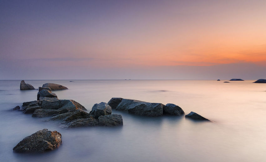 Rocks in sea at sunset