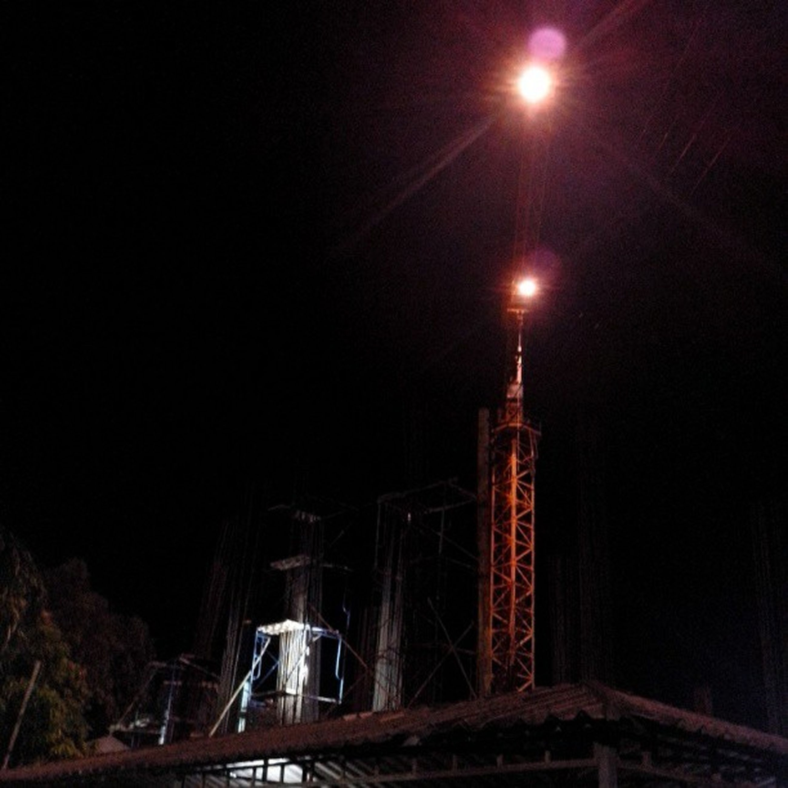 night, built structure, illuminated, architecture, low angle view, building exterior, tall - high, sky, city, tower, development, travel destinations, skyscraper, modern, outdoors, construction site, crane - construction machinery, connection, no people, capital cities