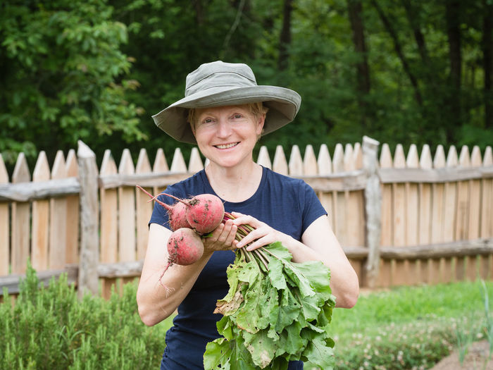 Portrait of smiling young woman holding vegetable