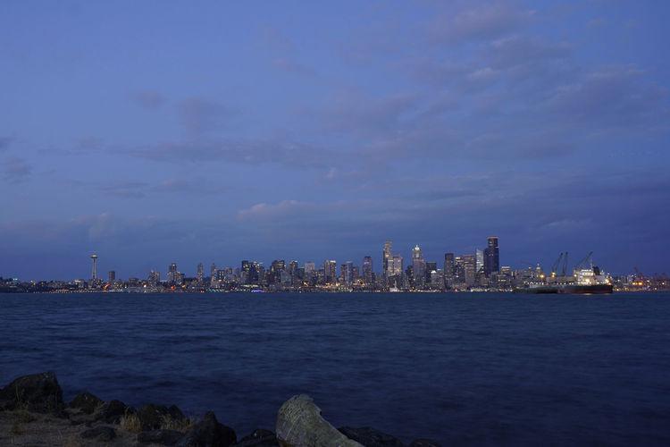 Sea by illuminated buildings against blue sky