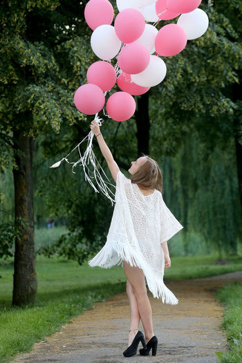 Woman holding pink and white helium balloons on footpath against trees at park