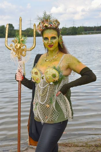 Portrait of woman standing in costume against lake