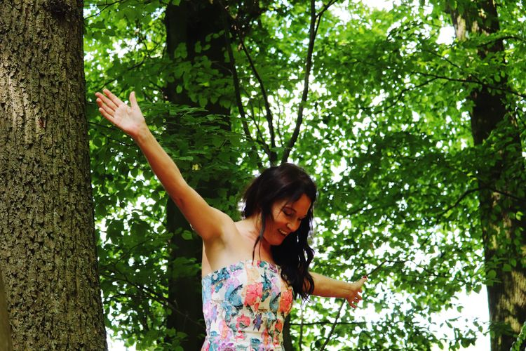 Happy woman with arms outstretched against trees