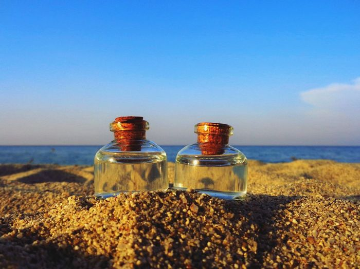Close-up of glass bottles on sand at beach