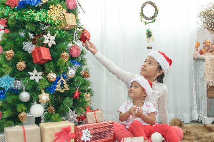Full length of happy girl in christmas tree