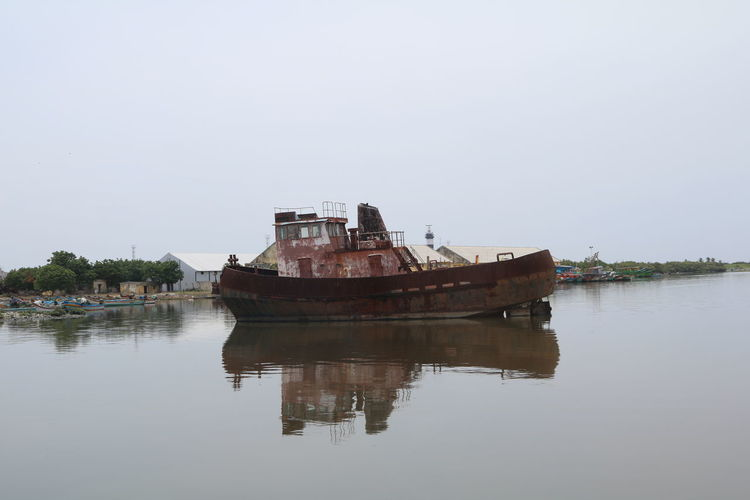 Boat in river against clear sky
