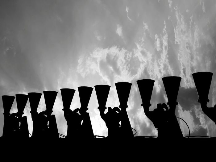 Low angle view of wine bottles against sky