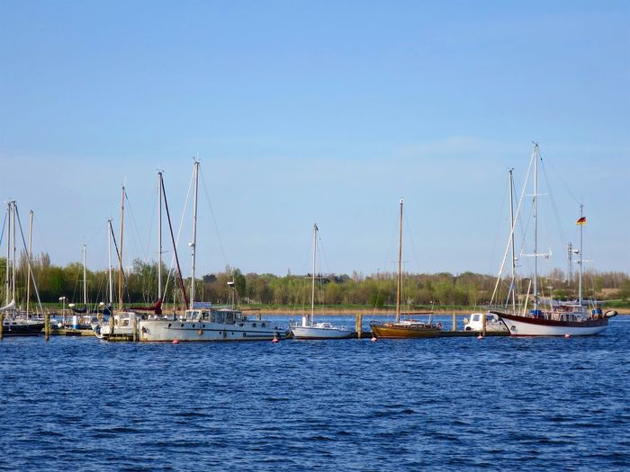 Anchored Beauty In Nature Blue Clear Sky Day Harbor Marina Mast Mode Of Transportation Moored Nature Nautical Vessel No People Outdoors Pole Sailboat Sea Sky Transportation Water Waterfront Yacht