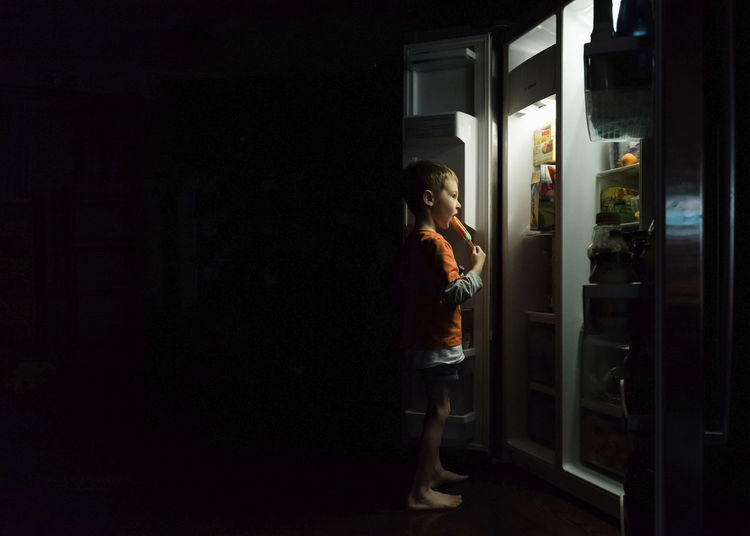 Side view of boy looking at entrance to at night